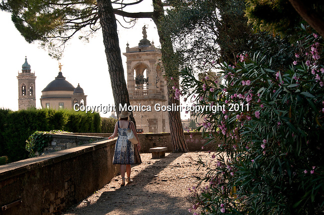 A woman walks through the park of the Rocca, The Castle of Bergamo, Italy at sunset