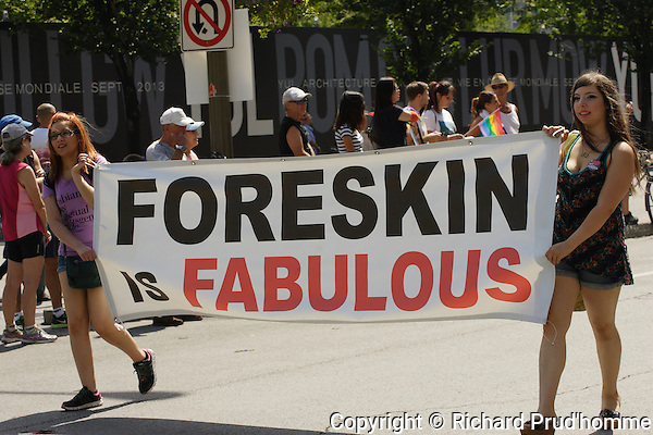 "Two young women carry a ""Foreskin is fabulous banner in the Pride Parade"