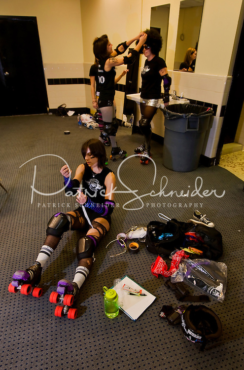 A roller girl tapes up her skates in the locker room during a Charlotte Roller Derby Girls event at Bojangles Arena in Charlotte, NC.
