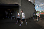 Home team players walking back to the dressing rooms at the Commonwealth Stadium at Meadowbank at the conclusion of the Scottish Lowland League match between Edinburgh City (white shirts) and city rivals Spartans, which was won by the hosts by 2-0. Edinburgh City were the 2014-15 league champions and progressed to a play-off to decide whether there would be a club promoted to the Scottish League for the first time in its history. The Commonwealth Stadium hosted Scottish League matches between 1974-95 when Meadowbank Thistle played there.