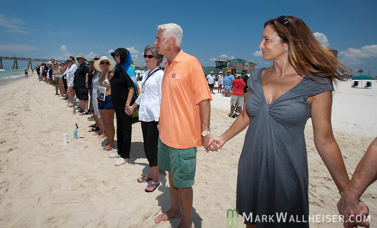 Florida Governor Charlie Crist and his wife Carole join several hundred people as they line Pensacola Beach for the Hands Across the Sand protest against offshore oil drilling June 25, 2010.