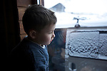 young siberian boy looking by the window at the cold winter in Angasolka guesthouse on the west side of the baikal