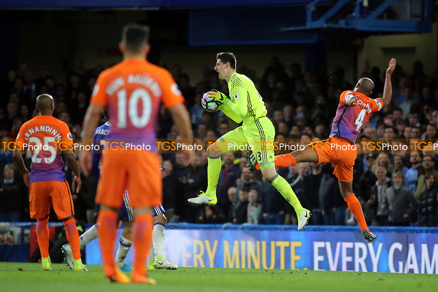 Chelsea goalkeeper, Thibaut Courtois, receives a painful  kick from Vincent Kompany of Manchester City during Chelsea vs Manchester City, Premier League Football at Stamford Bridge on 5th April 2017