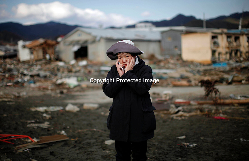 A woman reacts while using a mobile phone as she looks at her house destroyed by the tsunami in Kessenuma. TSUNAMI