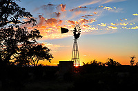 Texas Windmill at Sunset2 - As we were leaving Garner State Park area when we came upon this great big wind mill with it water tank just at sunset. So of course we stopped and captured this silouette of this windmill and water tank in a Texas landscape as the sun last twinkle shines through at the bottom before it went behind below the horizon. Wind mills in this area are much bigger than other areas I don't know but I suspect they have to be larger to bring up the water at a greater dept in the Texas Hill Country than else where.