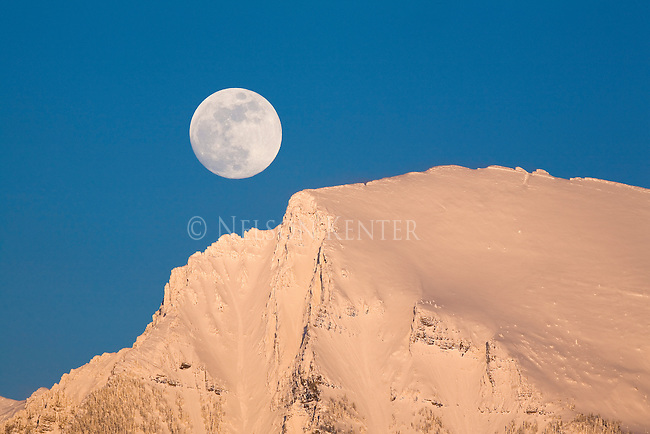 The full moon rise over the snow covered Mission Mountains in Montana