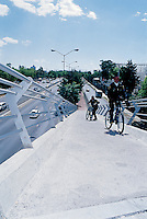 Two police try to ride up the steep incline of the Cyclopista which is the Mexico City bicycle path.  Many of the bridges had to be torn down and rebuilt because they were too steep.
