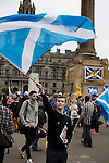 A young man waving a Scottish saltire flag above his head at a pro-independence gathering in George Square, Glasgow. The gathering brought together Yes Scotland supporters who favour Scotland leaving the union with the United Kingdom. On the 18th of September 2014, the people of Scotland voted in a referendum to decide whether the country's union with England should continue or Scotland should become an independent nation once again and leave the United Kingdom.