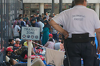 Security guard oversees illegal migrants in a transit zone at the main railway station Keleti in Budapest, Hungary on August 30, 2015. ATTILA VOLGYI