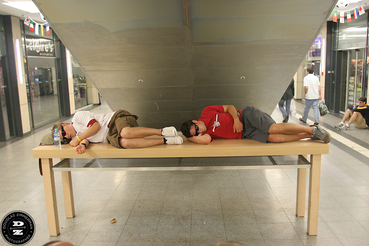USA National Soccer Team fans sleep on a table in the Mannheim main train station while waiting for a train the morning after the  USA's 1-1 draw with Italy in Kaiserslautern Germany.