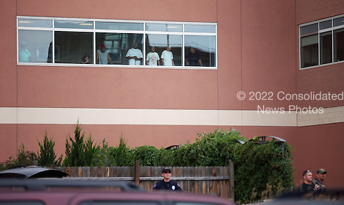 People watch from a second floor window as United States President Barack Obama's motorcade arrives at University of Colorado Hospital July 22, 2012 in Aurora, Colorado. Obama met with victims of last Friday's movie theater mass shooting. Police in Aurora, a suburb of Denver, say that James Holmes, 24, in custody after he is suspected of killing 12 people and injuring 59 during a midnight screening of 'The Dark Knight Rises' last Friday.  .Credit: Chip Somodevilla / Pool via CNP