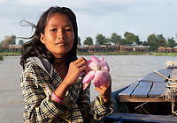 A local Khmer girl playing with a Lotus flower. Lotus flower fields lake and farm north west of Battambang