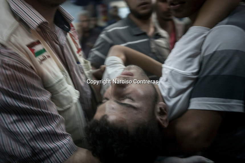 """August 22, 2014 - Gaza City, Gaza strip, Palestinian Territory: A Palestinian man is carried out to the emergency ward at Al-Shifa hospital after he was injured during an airstrike in Al-Sabra neighbofhood as """"Protective Edge"""" Israeli military operation continues in the Gaza strip. (Narciso Contreras/Polaris)"""