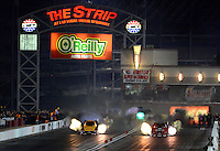 Oct. 26, 2012; Las Vegas, NV, USA: NHRA funny car driver Cruz Pedregon (right) races alongside Jeff Arend during qualifying for the Big O Tires Nationals at The Strip in Las Vegas. Mandatory Credit: Mark J. Rebilas-