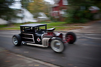 Blurred photo of 1927 hot rod traveling down side street.