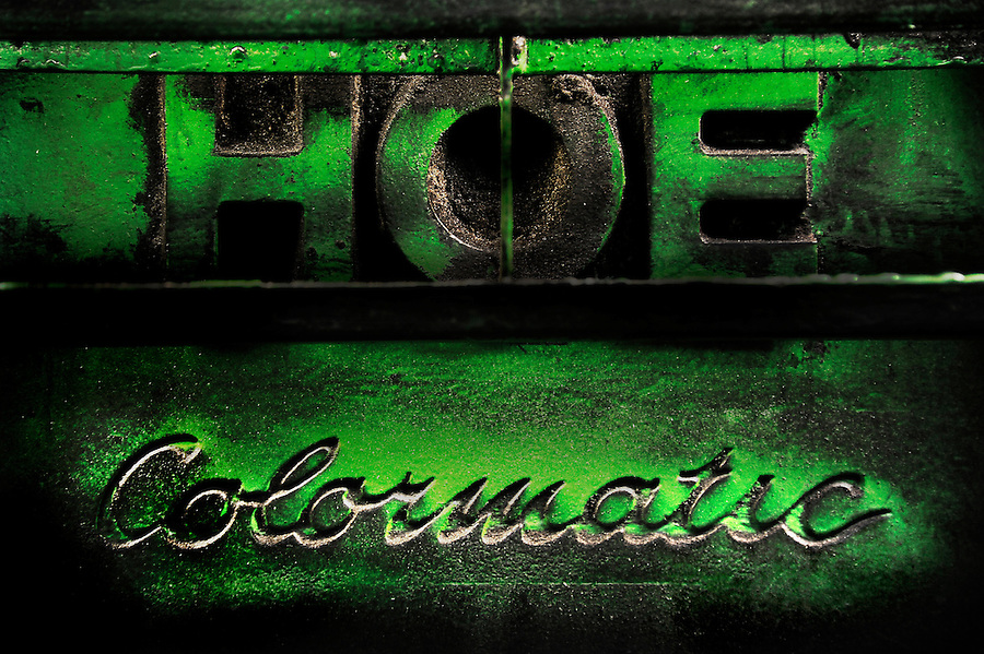 "The cast iron base of a decades old newspaper press with  ""HOE"" and ""Colormatic"" imprents under a coat of newsprint dust and worn green paint. copyright JimMendenhallPhotos.com 2013"