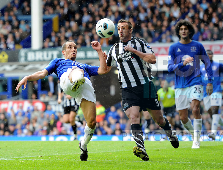 Leon Osman of Everton attempts an overhead kick as Jose Enrique of Newcastle United closes in