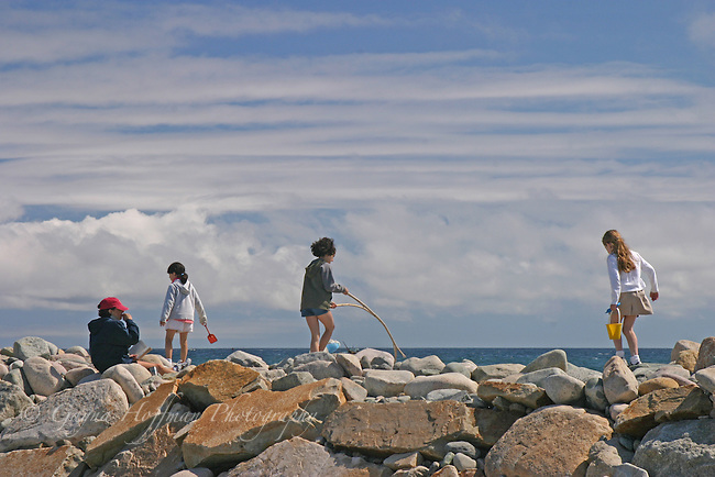 Children playing on rocky coastal barrier wall. Scituate, MA, New England, U.S.
