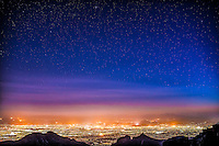 Colorful city orange glow over Tucson from the Santa Catalinas mountains with the city below and bright stars became visible above the city glow. This landscape really displays the different layers of light over the city.