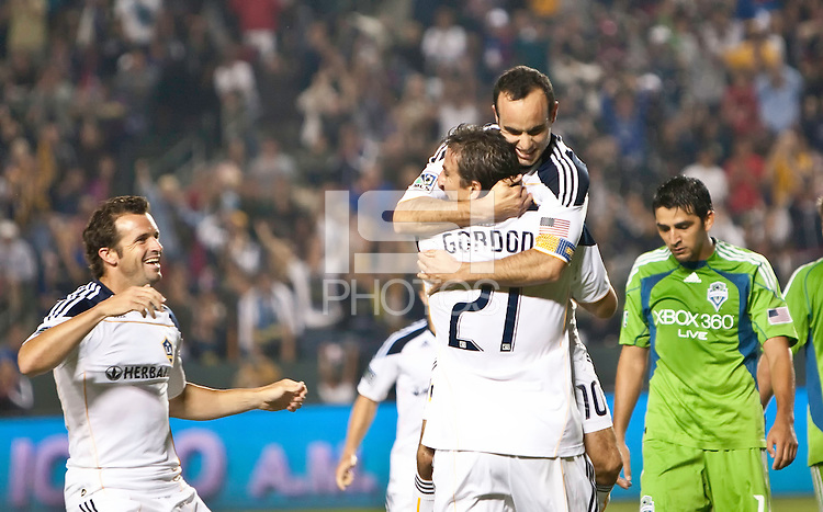 LA Galaxy midfielder Landon Donovan (10) gives a hug to forward Alan Gordon (21) as midfielder Chris Klein looks on after a goal during the second half of the game between LA Galaxy and the Seattle Sounders at the Home Depot Center in Carson, CA, on July 4, 2010. LA Galaxy 3, Seattle Sounders 1.