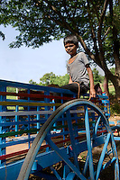 A boy, about 7-8 years old, on a blue bullock cart. The bullocks have been sent to graze, while the boy who  can drive the cart independently, helps in the maintenance work.