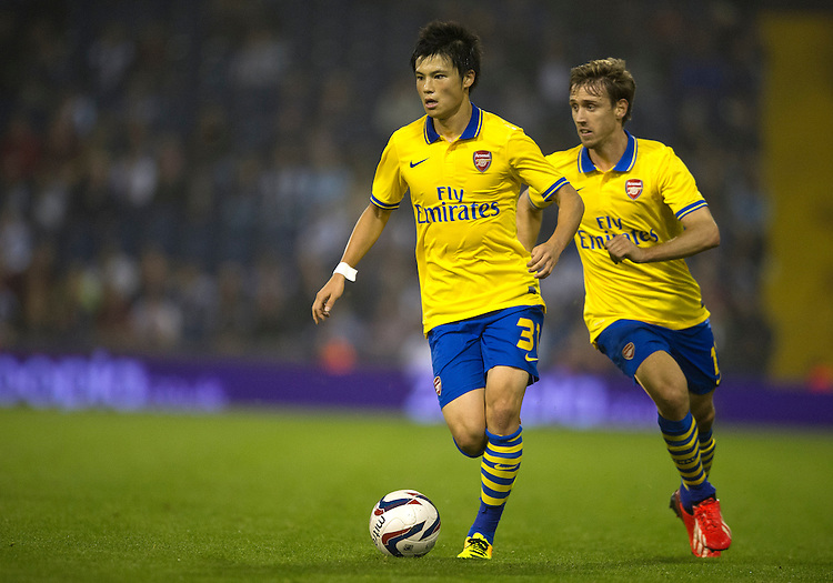 Arsenal's Ryo Miyaichi tracked by with team-mate Nacho Monreal<br /> <br /> Photo by Stephen White/CameraSport<br /> <br /> Football - Capital One Cup Third Round - West Bromwich Albion v Arsenal - Wednesday 25th September 2013 - The Hawthorns - West Bromwich<br />  <br /> &copy; CameraSport - 43 Linden Ave. Countesthorpe. Leicester. England. LE8 5PG - Tel: +44 (0) 116 277 4147 - admin@camerasport.com - www.camerasport.com