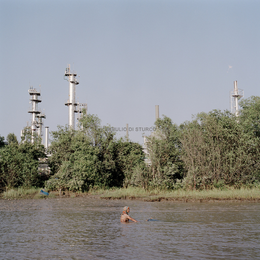 a woman fishing in front of an oil refinery along the Ganges in the sunderbans