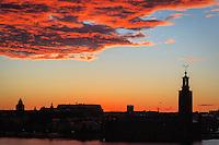Röda moln efter kraftig regnskur över Stadshuset i Stockholm