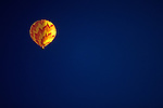 One yellow and orange hot air balloon floating in a deep blue sky early morning lift-off on a sunny morning Kent Washington State USA