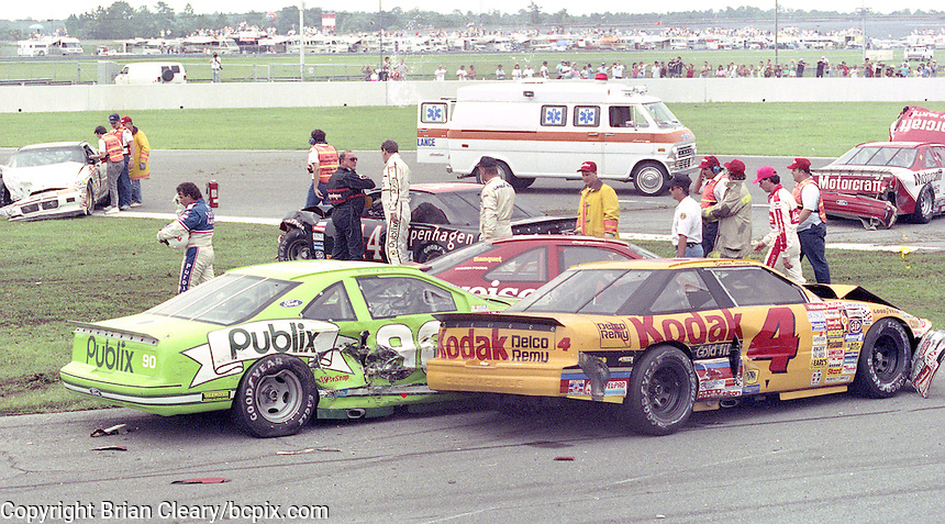 Drivers and safety crew members walk among the wreckage after a 24 car crash early in the Pepsi 400, Daytona International Speedway, Daytona Beach, FL July 7, 1990.  (Photo by Brian Cleary/www.bcpix.com)