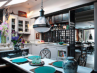 Beyond the living area, the kitchen is enclosed with black patinated panels, their wooden grid in a Chinese style