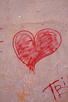 A red love heart spray-painted onto a wall