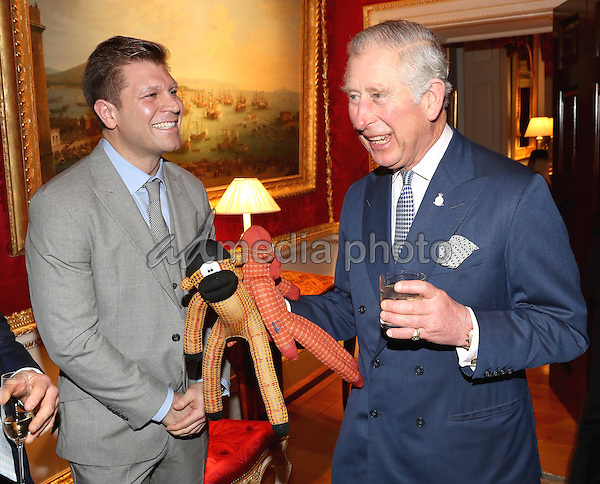 14 December 2016 - Prince Charles, Prince of Wales is presented with two sock monkeys by Ryan Palmer of the London Sock Co for Prince George and Princess Charlotte at the Style for Soldiers Christmas Reunion Party at Spencer House in London. The Prince of Wales met injured servicemen and women who have been helped by the charity, and others who have supported them. His Royal Highness will also meet some of the charity's patrons and ambassadors. Photo Credit: Alpha Press/AdMedia