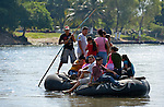 Migrants and others cross the Suchiate River where it forms a border between Guatemala and Mexico. The river crossing is part of the main route that Central American migrants follow on their way north.