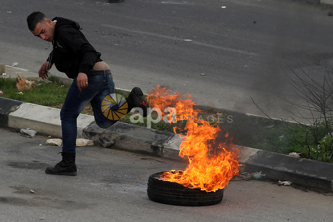 A Palestinian protester burns tires during clashes with Israeli soldiers outside Israel's Ofer military prison following a protest in support of prisoners on hunger strike in Israeli prisons, near Ramallah on February 19, 2013. Some 800 Palestinians serving time in Israeli jails were refusing food in solidarity with four fellow inmates who have been on long-term hunger strike, officials said. Photo by Issam Rimawi