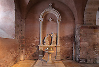 Baptismal font and statue of Christ as a pilgrim, in the entrance to the left of the portal in the North ambulatory, in the Abbatiale Sainte-Foy de Conques or Abbey-church of Saint-Foy, Conques, Aveyron, Midi-Pyrenees, France, a Romanesque abbey church begun 1050 under abbot Odolric to house the remains of St Foy, a 4th century female martyr. The church is on the pilgrimage route to Santiago da Compostela, and is listed as a historic monument and a UNESCO World Heritage Site. Picture by Manuel Cohen