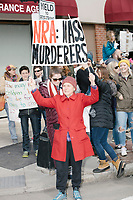 "People take part in the March For Our Lives protest, walking from Roxbury Crossing to Boston Common, in Boston, Massachusetts, USA, on Sat., March 24, 2018, in response to recent school gun violence. Here a woman holds a sign reading, on one side, ""NRA: Mass Murderers"" and ""Repeal 2nd Amendment"" on the other."