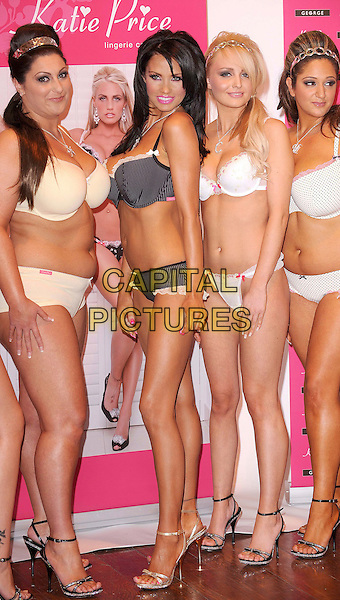 """KATIE PRICE aka JORDAN.Models with friends at a photocall to launch """"Katie Price Lingerie Collection"""" - a new range to be sold in all George at Asda stores - held at Worx Studio, Fulham, London, England, .March 5th 2008..full length black and white pinstripe bra knickers underwear pink lipstick nails  tanned boob job gold sandals shoes poster A initial necklace.CAP/BEL.?Tom Belcher/Capital Pictures"""