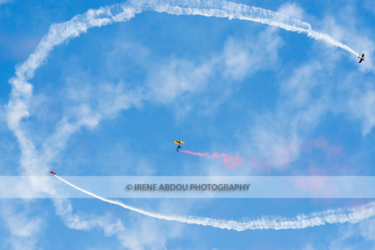 Two planes circle a Golden Knights parachutist at the 2008 Joint Service Open House air show at Andrews Air Force Base, Maryland.