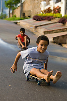 Two boys race down a steep hill on skateboards in Trinidad & Tobago