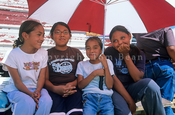 Girls watch horse races from under umbrella, during Yazzie Benefit Horse Race, 6/19/05, at Jeddito, Navajo Indian Nation, Arizona, AGPix_0632..