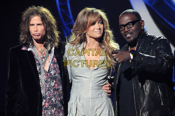 "STEVEN TYLER, JENNIFER LOPEZ & RANDY JACKSON.""American Idol"" Season 10 Judges Panel Announcement held at The Forum, Inglewood, California, USA, .22nd September 2010..half length tv studio on stage  grey gray silver catsuit jumpsuit  sparkly  wavy hair pink floral print shirt jacket hand finger pointing gesture leather glasses .CAP/ADM/BP.©Byron Purvis/AdMedia/Capital Pictures."