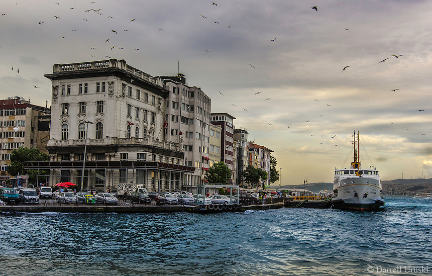 Fine Art Landscape Photograph of the Bosphorus Strait in Istanbul, Turkey. The dramatic lighting on the buildings with the birds flying overhead against the backdrop of the breaking clouds set the mood for this artistic photograph.