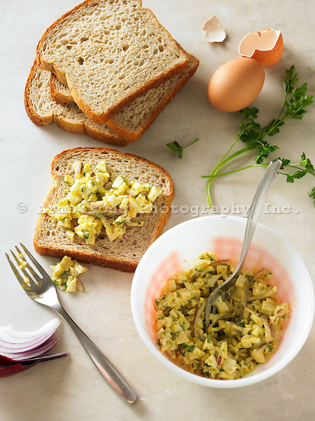 Preparing a sandwich: Bowl of curried egg whites, slices of whole wheat bread, fork, egg and eggshell, red onion slices, and parsley sprig.