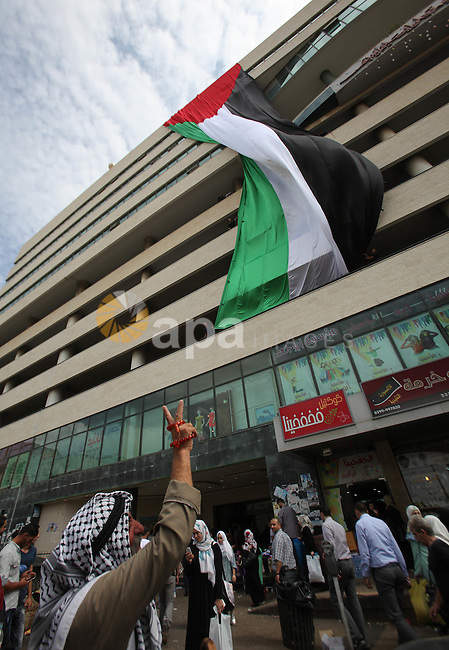 A Palestinian man flashes victory sign as he walks past his national flag hanged on a building during an event to support Palestinian President Mahmoud Abbas in the West Bank city of Nablus on September 30, 2015. Abbas has circulated a hard-hitting critique of alleged Israeli violations of the 20-year-old Oslo accords and subsequent agreements ahead of his speech to the UN general assembly in New York later on Wednesday. Photo by Nedal Eshtayah