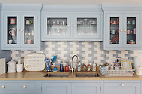 Pale blue wall units with glass doors store crockery above the kitchen sink