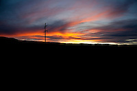 A power pole stands in silhouette, its high voltage cables tracing thin lines across a sunset sky in Paradox Valley, Colorado.