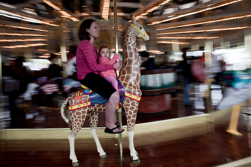 A mother takes her baby for a ride on a giraffe on a carousel at a county fair in Portland.