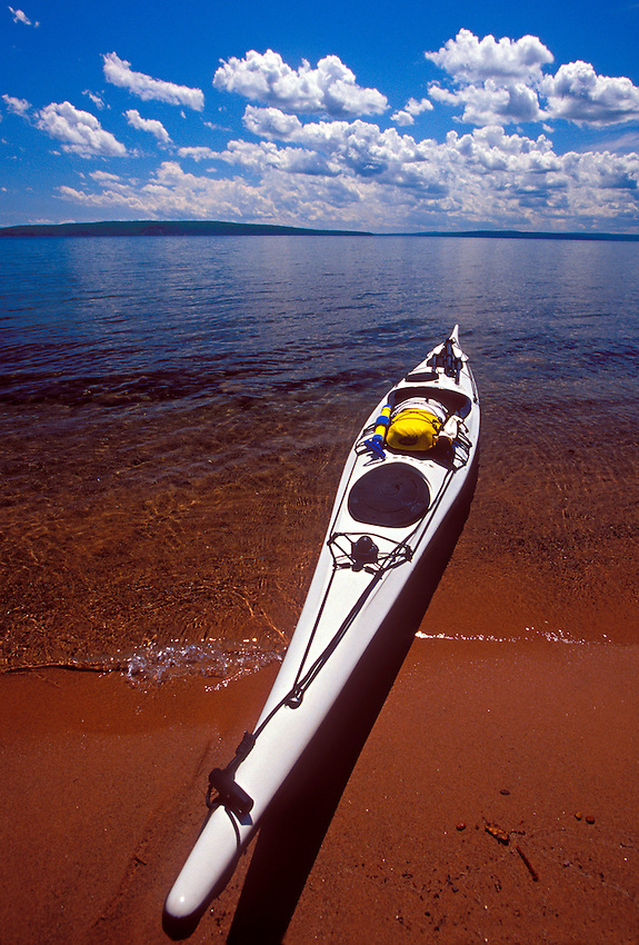 A sea kayak beached on Bear Island under puffy cumulous clouds in Apostle Islands National Lakeshore near Bayfield, Wis.