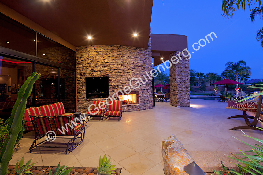 Night time view of outdoor living areas and swimming pool of luxury estate